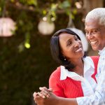 Senior African American couple dancing in their backyard, close up